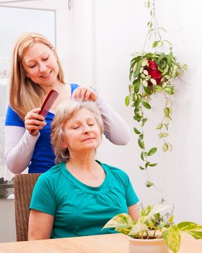 caregiver combing the hair of the senior woman