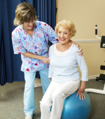 caregiver assisting senior woman in exercise
