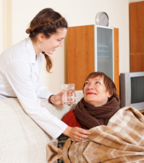 caregiver giving water to the old woman